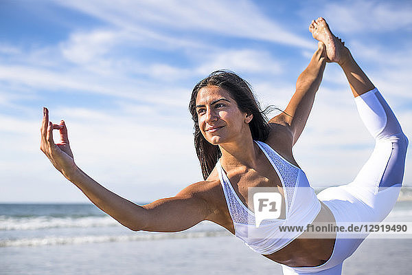 Photograph of young woman standing on one leg while doing yoga on beach