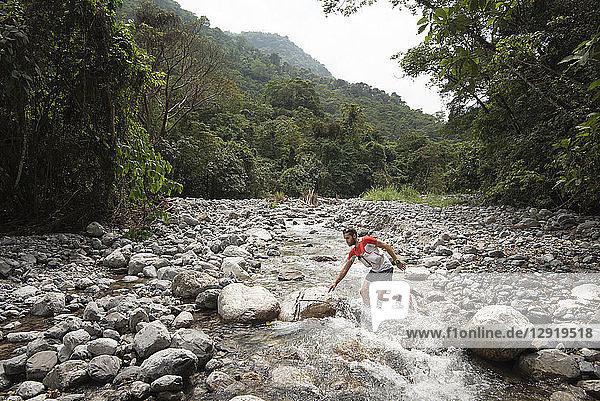 One man crossing a river at the area of Los Limones in Xicotepec de Juarez  Puebla  Mexico.
