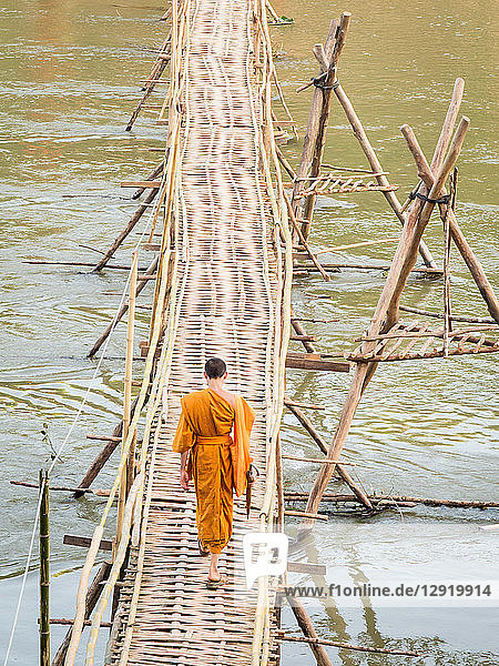 Orange-clad Buddhist monk crossing a bamboo bridge  Luang Prabang  Laos  Indochina  Southeast Asia  Asia