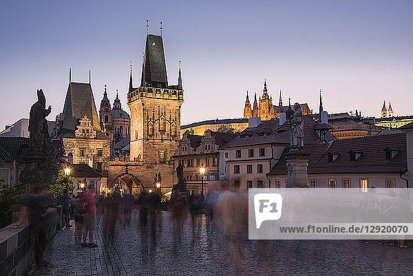Charles Bridge  Lesser Towers  and Prague Castle at night with blurred pedestrians  UNESCO World Heritage Site  Prague  Czech Republic  Europe