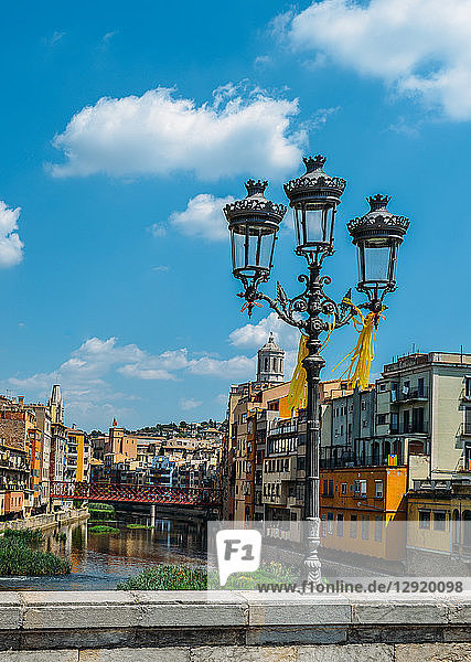 Colourful houses on the embankment of the River Onyard in historic centre and Eiffel Bridge in far background  Girona  Catalonia  Spain  Europe