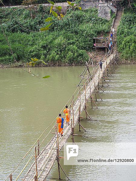 Orange-clad Buddhist monks crossing a bamboo bridge  Luang Prabang  Laos  Indochina  Southeast Asia  Asia
