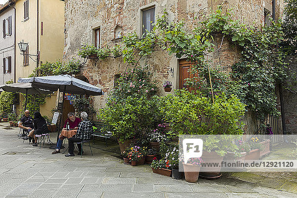 People sitting outside at a restaurant within a small courtyard surrounded by flowers in Pienza  Tuscany  Italy  Europe