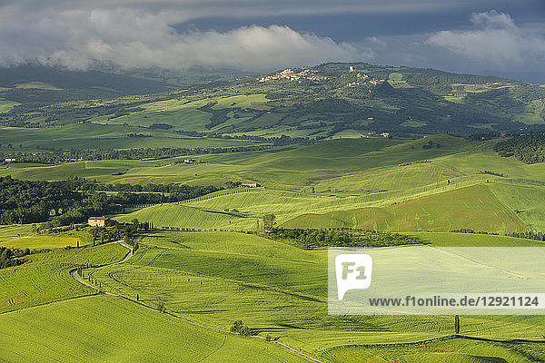 Looking across the Val d'Orcia to the historic towns of Rocca d'Orcia and Castiglione d'Orcia with clouds lingering beyond  UNESCO World Heritage Site  Tuscany  Italy  Europe