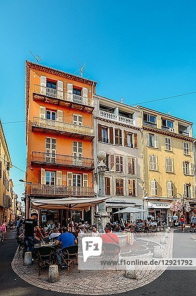Tourists at a cafe on a street corner and traditional Provencal architecture in Antibes  Cote d'Azur  Provence  French Riviera  France  Europe