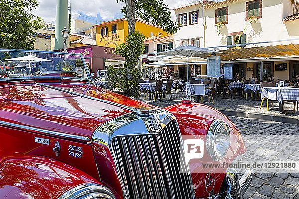 View of red vintage MG car in front of traditional Al Fresco restaurant in old town  Funchal  Madeira  Portugal