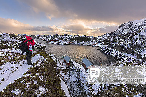 Photographer on rocky peak  Nusfjord  Lofoten Islands  Nordland  Norway