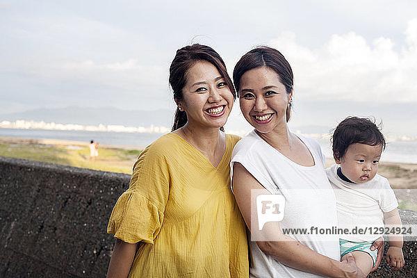 Porträt von zwei Japanerinnen  eine mit einem Kleinkind  die auf einer Promenade am Meer stehen und in die Kamera lächeln.