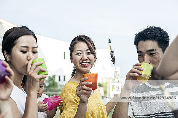 Group of Japanese men and women standing outdoors  drinking from plastic beakers.