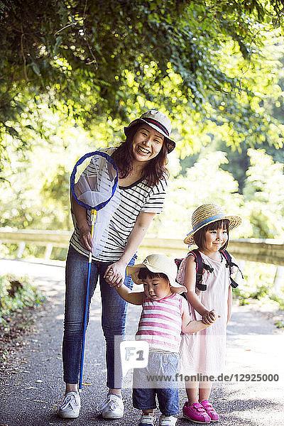Lächelnde Japanerin mit Schmetterlingsnetz und zwei Mädchen mit Sonnenhüten stehen auf dem Weg und schauen in die Kamera.
