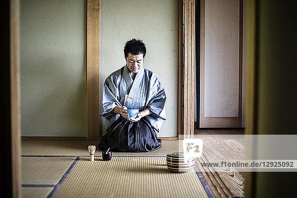 Japanischer Mann in traditionellem Kimono  kniend auf Tatami-Matte  eine Teeschale haltend  während der Teezeremonie.