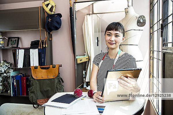 Japanische Modedesignerin  die in ihrem Atelier arbeitet und in die Kamera lächelt.
