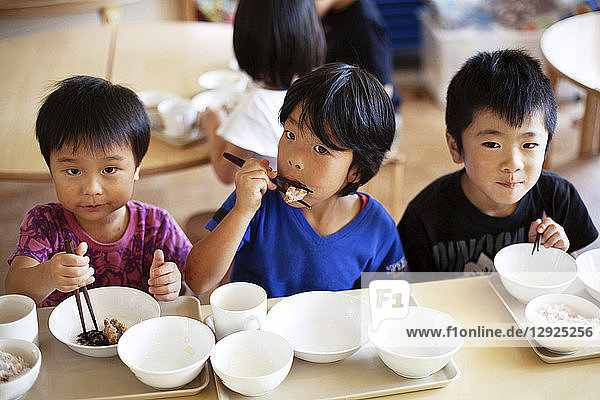 High angle view of three boys sitting at a table in a Japanese preschool  eating with chopsticks.