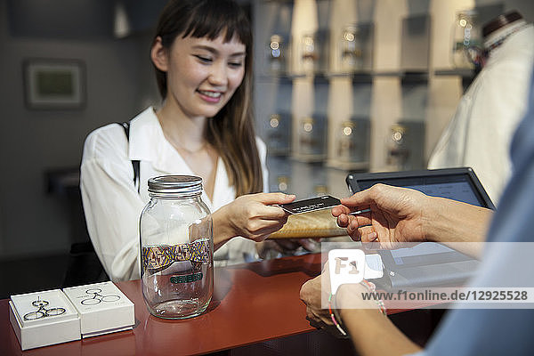 Lächelnde japanische Frau  die in einem Bekleidungsgeschäft am Schalter steht und mit Kreditkarte bezahlt.