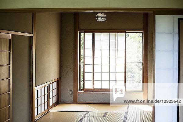 Innenansicht eines traditionellen japanischen Hauses mit Tatami-Matten und undurchsichtigen Schiebetüren.