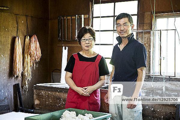 Eine japanische Frau und ein japanischer Mann stehen in einer Washi-Werkstatt an einem Bottich mit Zellstoff  den Grundstoffen auf pflanzlicher Basis für die Papierherstellung.