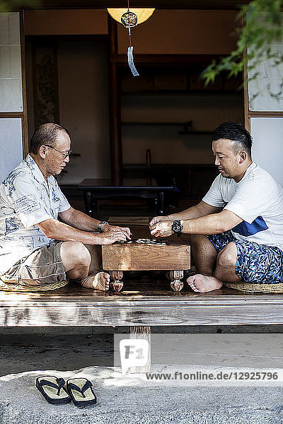 Two Japanese men sitting on floor on porch of traditional Japanese house  playing Go.