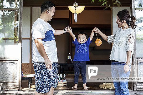 Japanischer Mann und Frau stehen auf der Veranda eines traditionellen japanischen Hauses  spielen mit einem kleinen Jungen und halten sich an den Händen.