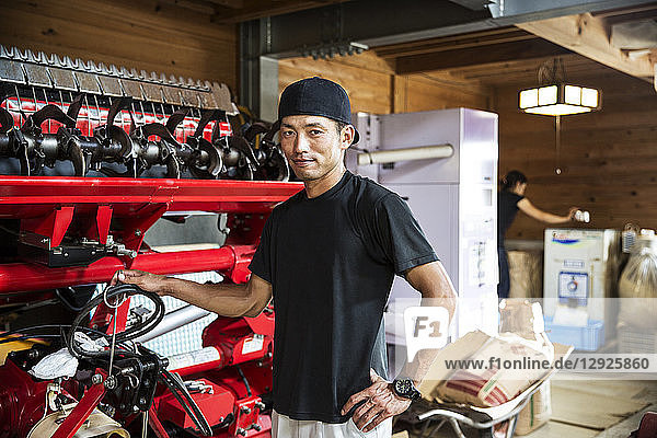 Japanese farmer wearing black cap standing next to agricultural machine  smiling at camera.
