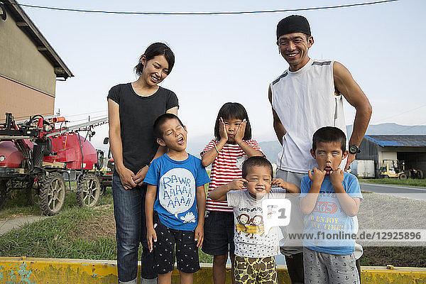 Porträt eines lächelnden japanischen Bauern  seine Frau und vier Kinder stehen in ihrem Hof  die Kinder ziehen vor der Kamera Gesichter.