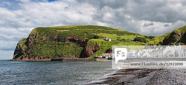 Stone beach and row of white houses of Pennan coastal fishing village on North Sea in Aberdeenshire Scotland UK with Black Hill sea cliff.