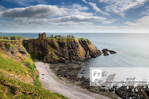 Pebble beach at Old Hall Bay North Sea with Donnottar Castle Medieval clifftop fortress ruins near Stonehaven Scotland UK.
