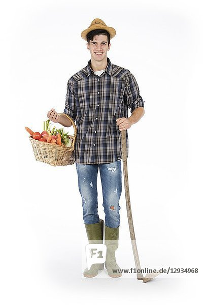Young farmer holding one arm holding a basket with fruit and vegetables  with the other a hoe  he is wearing a straw hat  checked shirt and green rubber boots.