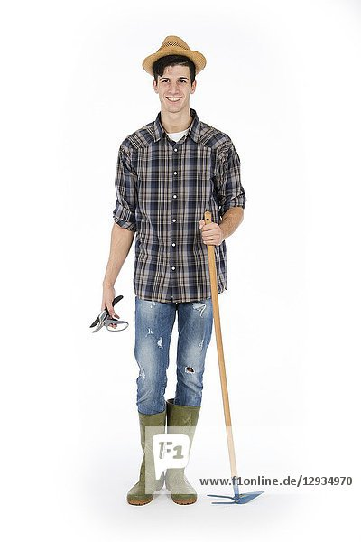Young farmer with shears and hoe in hands  he is wearing a straw hat  checked shirt and green rubber boots.