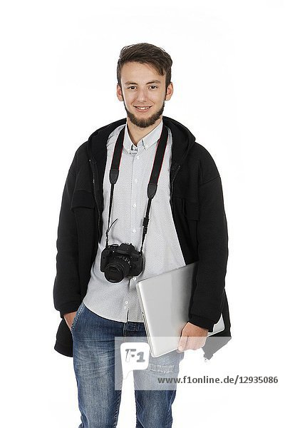 Nerd boy with camera around his neck and computer under his arm  he is standing in the studio and is wearing casual clothes.