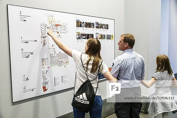 United Kingdom Great Britain England  London  Trafalgar Square  The National Gallery  art museum  inside interior  man  floor plan  directions  levels  man  woman  girl  family  pointing
