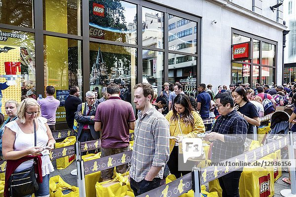 United Kingdom Great Britain England  London  Leicester Square  Lego Store  plastic construction toys brand  shopping  outside  roped line queue  special event  man  woman  waiting