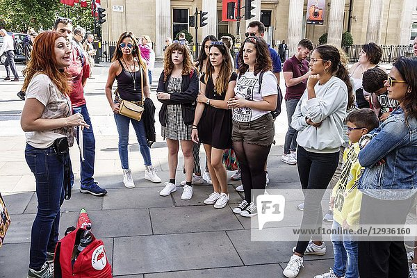 United Kingdom Great Britain England  London  Leicester Square  plaza  Strawberry Walking Tour  speaking  listening  woman  boy