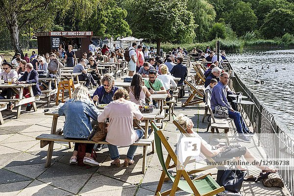 United Kingdom Great Britain England  London  Hyde Park Royal Parks  Serpentine Bar & Kitchen  restaurant  picnic tables  alfresco dining  Burgers Soft Drinks & Craft Beer food kiosk  outside seating lakeside deck eating drinking  man  woman