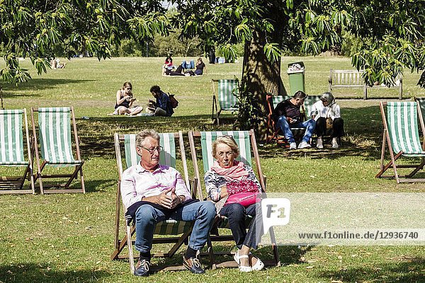 United Kingdom Great Britain England  London  Royal Parks  Hyde Park  park  green space  lawn  tree  deck chairs  man  woman  couple  mature  basking in sun  sunbathing