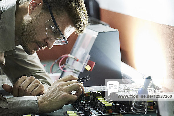 Engineer soldering circuit board in office