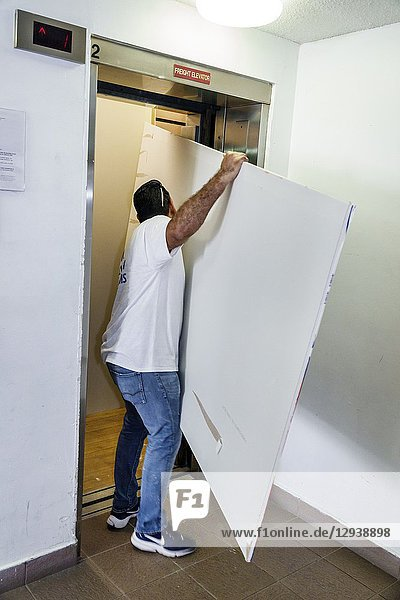 Florida  Miami Beach  contractor  renovation  repair  drywall  Hispanic  man  fitting service elevator  working