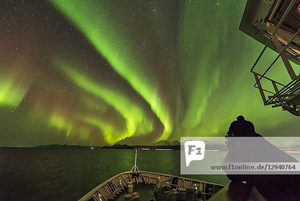 The Northern Lights exhibiting with green and red curtains to the northeast off the forrward deck 5 of the Nordlys with a photographer grabbing a shot. Looking towared Capella  Auriga and Perseus.Taken from the Hurigruten ship the m/s Nordlys north of Tromsø on October 24  2017.This is a single 2-second exposure with the Sigma 14mm Art lens at f/1. 8 and Nikon D750 at ISO 6400.