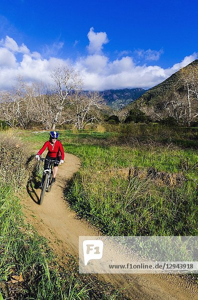 Female mountain biker in Sycamore Canyon  Point Mugu State Park  California USA.