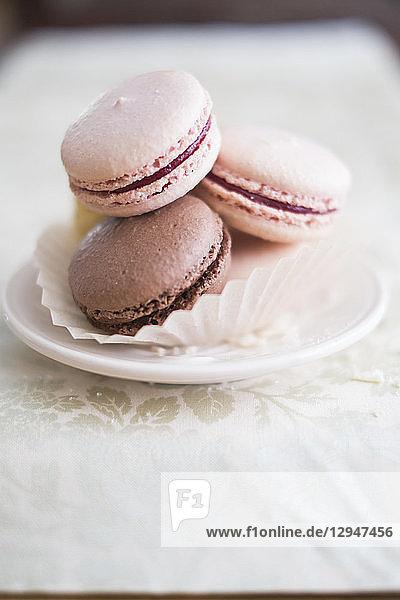 Verschiedene französische Macarons in Papierförmchen auf Gebäckteller