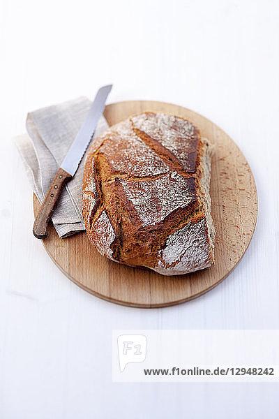 Weizenmischbrot mit Brotmesser auf Holzbrett
