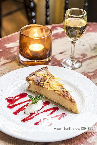 Ein Stück Käsekuchen auf Desertteller  Dessertwein und Kerze im Hintergrund