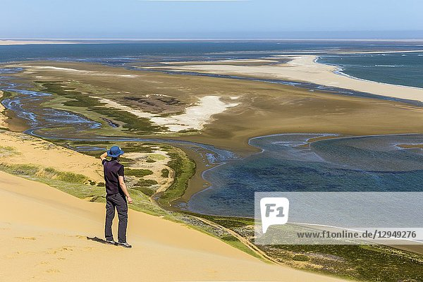 Man admiring Sandwich Bay from the top of the sand dunes Namib Naukluft National Park Namibia Africa.