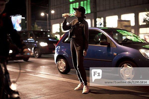 Woman drinking from bottle on street in Berlin  Germany