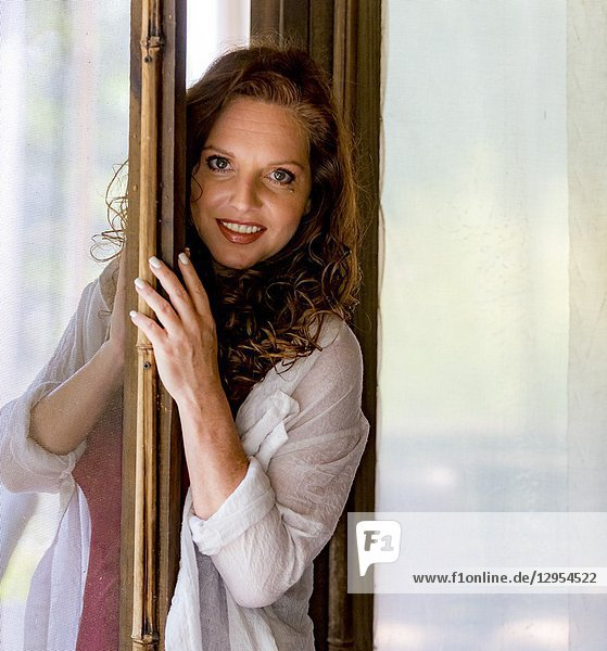 Portrait of a pretty redheaded woman looking through a screen door  smiling at the camera.
