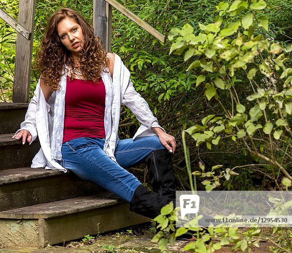 Casual portraits of a pretty 39 year old redheaded woman sitting on steps outdoors.