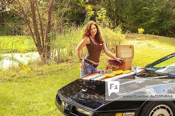 A pretty 39 year old redheaded woman standing by a black Corvette with a picnic basket on the hood of the car.