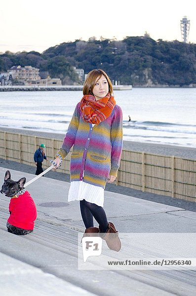 Japanese Girl poses with dog in Enoshima  Japan. Enoshima is an area where is famous about the beach.