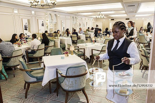 United Kingdom Great Britain England  London  West End St James's  Fortnum & Mason  shopping  inside interior  luxury upmarket department store  Diamond Jubilee Tea Salon  restaurant  tables  afternoon tea  Black  woman  waitress  carrying three-tiered dessert stand plates