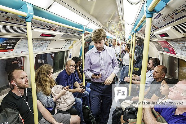 United Kingdom Great Britain England  London  underground subway tube  public transportation  train  carriage  inside  commuters  passenger rider  man  woman  Bakerloo Line  man  woman  commuters riders passengers  using smartphone