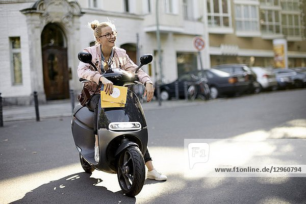 Woman on motor scooter  holding city tour guide map  in Berlin  Germany